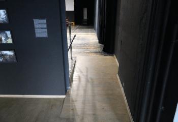 Zdjęcie. Drewniana podłoga z łagodnym podjazdem do sali. Po lewej stronie podjazdu poręcz. Czarne ściany.
