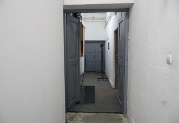 Zdjęcie. Otwarte szare drzwi. Za nimi korytarz z kolejnymi drzwiami. Po prawej stronie wieszak na ubrania.
