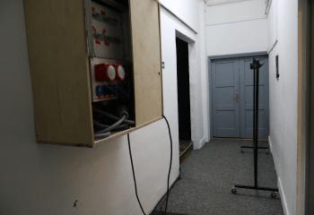 Zdjęcie. Korytarz. Po prawej stronie wieszak na ubrania i zamknięte drzwi. Po lewej stronie na ścianie wisi drewniana skrzynka z kablami.