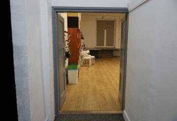 Zdjęcie. Szare, dwuskrzydłowe drzwi otwarte na oścież. Za nimi wnętrze sali.