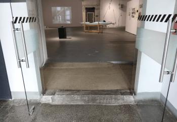 Zdjęcie. Korytarz. Otwarte szklane drzwi. Podłoga z niewielkim podjazdem. W tle wnętrze sali wystawowej.