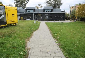 Zdjęcie. Na pierwszym planie chodnik z betonowej kostki, prowadzący do budynku galerii. Po lewej stronie widać fragment żółtego kiosku. Po obu stronach chodnika trawnik.