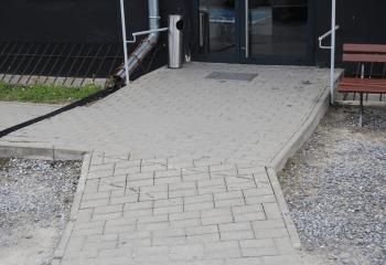Zdjęcie. Na pierwszym planie chodnik z kostki betonowej z łagodnym podjazdem prowadzącym do drzwi wejściowych.