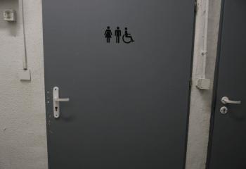 Zdjęcie. Szare drzwi toalety z czarnymi oznaczeniami.