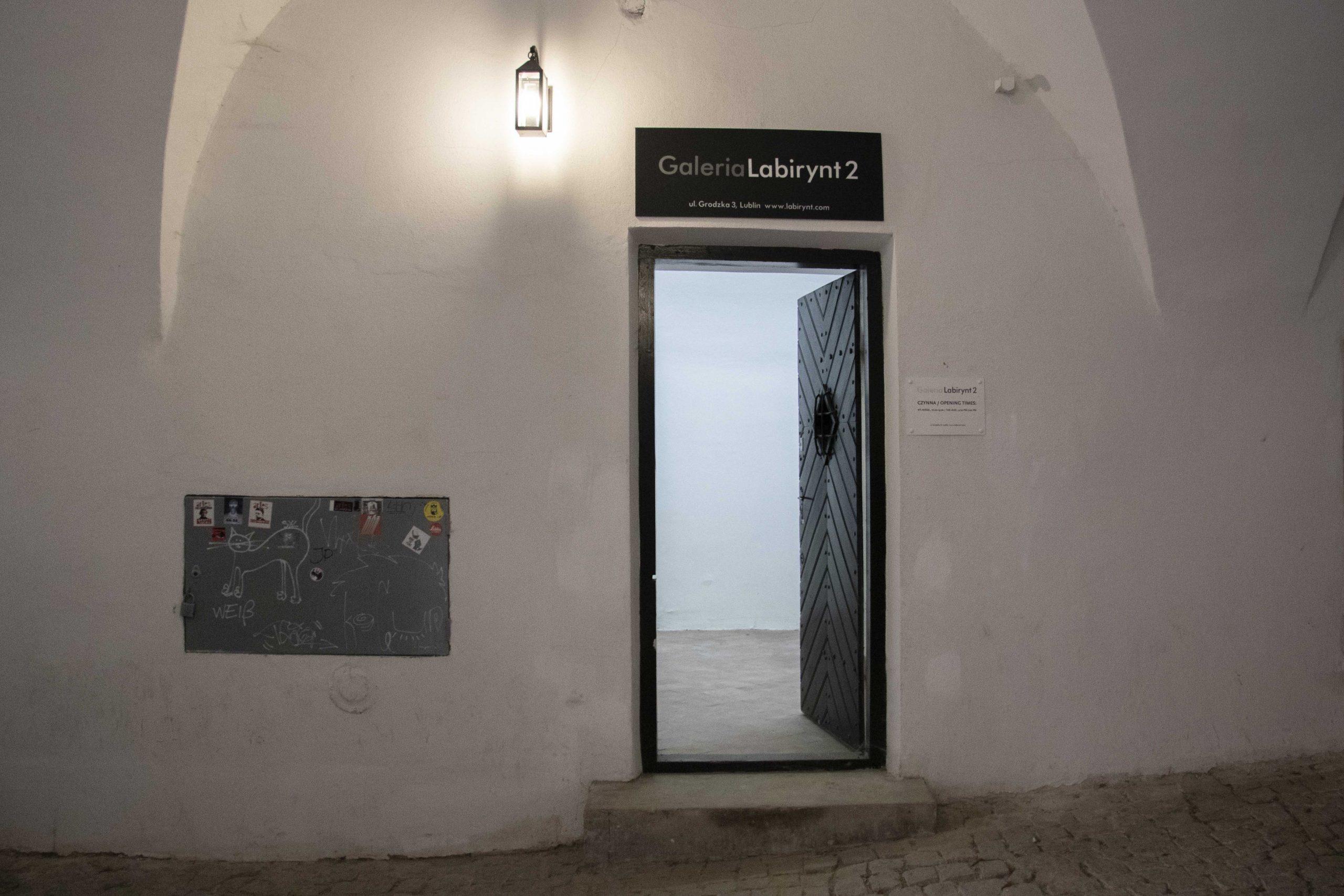 zdjęcie wejścia do galerii labirynt 2 - biała ściana i drzwi